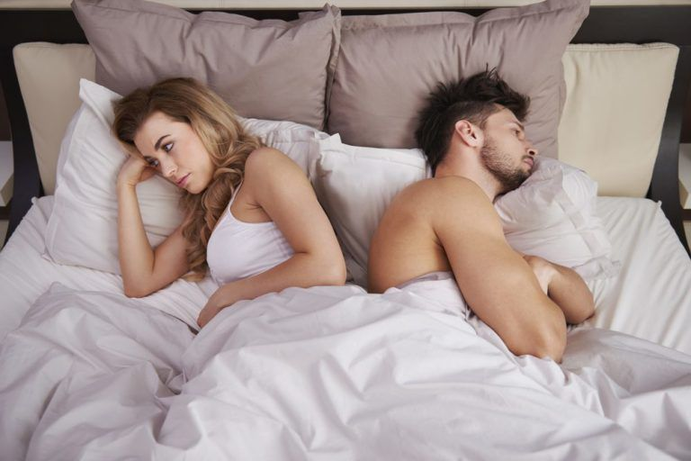 Couple in bed with their backs to each other frustrated from erectile dysfunction